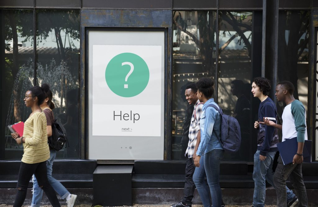 People Walking Past a Help Sign