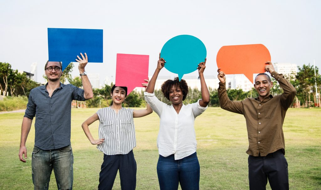 Four People Standing on Green Grass Field with Messages