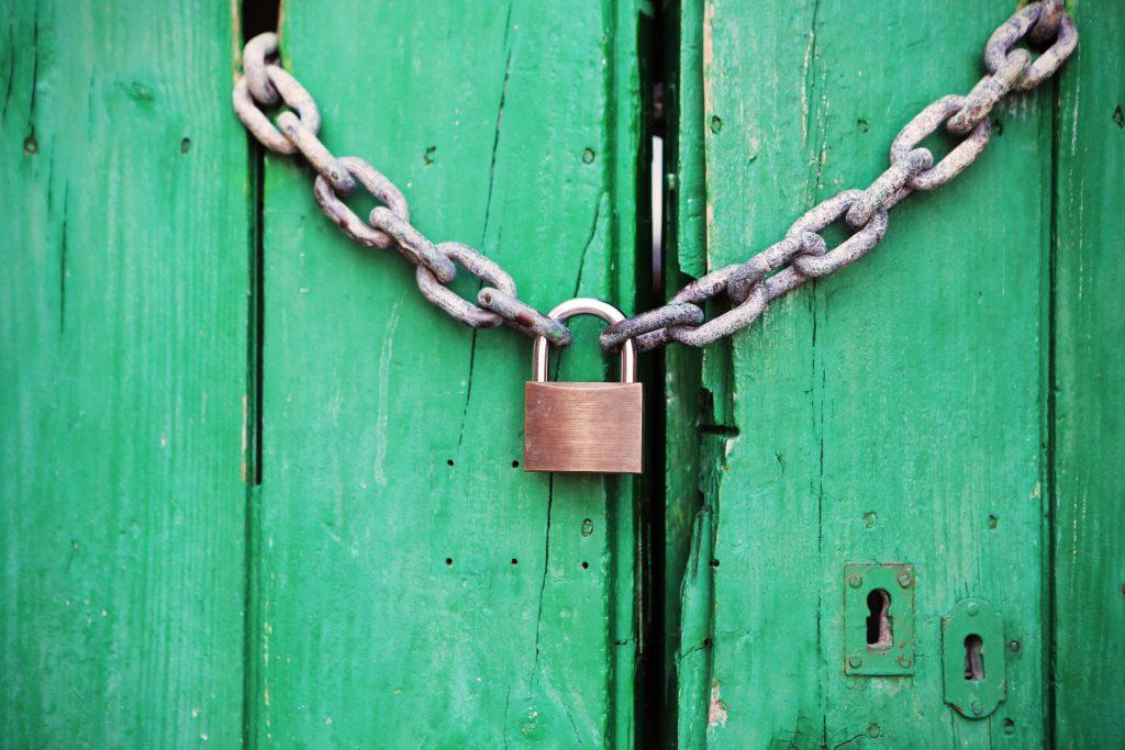 Lock and Chain on Wooden Door